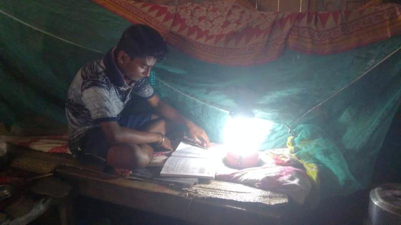 Zerstörung-und-Hilfe-Junge-mit-Solar-Lampe-unter-Moskitonetz