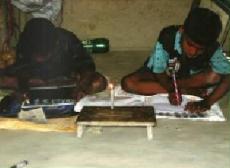 Kinder machen im Schein einer Kerze ihre Hausaufgaben (Foto: KMWSC)