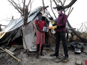 Alles verloren - und nur Zeltplanen als Unterschlupf: eine Familie erhält eine Solar-Lampe. Wegen Corona mit Handschuhen